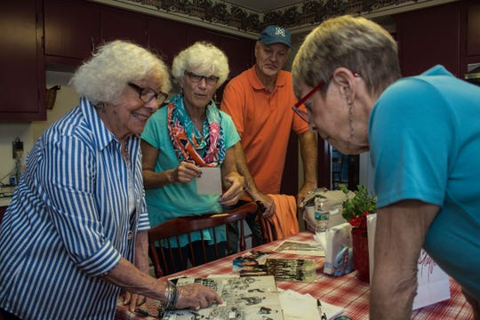 (L-R) Bunny Zuber,  Karen Patrick Mackolin, Wally Patrick, and Susan Zuber looking over family photos.