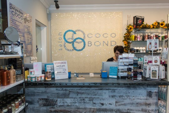 Manager Christie Citsay of Salon CoCo Bond works at the front desk of the Shrewsbury shop.