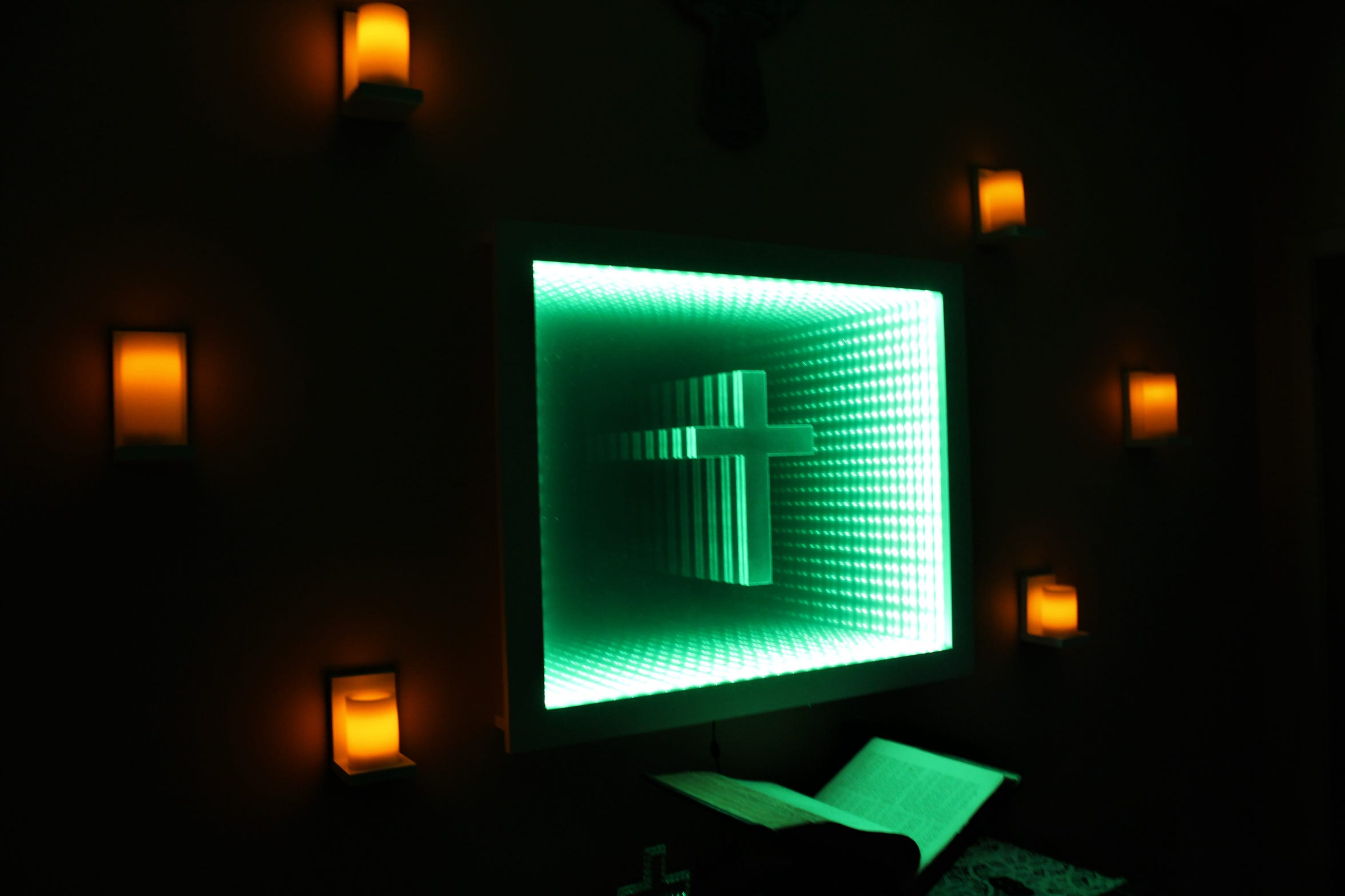 Six candles encircle the infinity cross mirror, with changing colors illuminating a Bible open below it.
