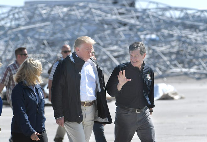 President Donald Trump walks with North Carolina Gov. Roy Cooper on the tarmac at Marine Corps Air Station at Cherry Point in Havelock, NC for a briefing on Hurricane Florence on Wednesday, Sept. 19, 2018.