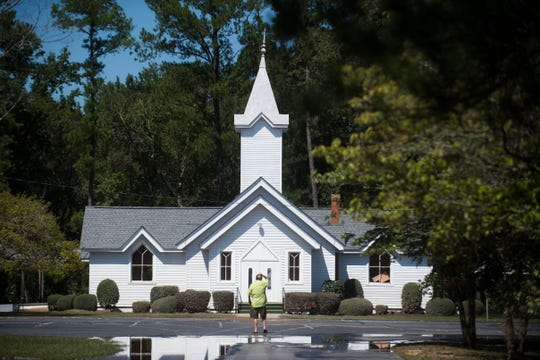 Ronnie Mayes scratches his head as he looks at the church he's attended his entire life, the Presbyterian Church of the Covenant, which he is an elder at, in Spring Lake, N.C., on Sept. 19, 2018.  The church was damaged from the Little River which flooded due to Florence.