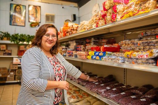 Conchi Molina stocks the shelves and greets the customers at La Catrachita .