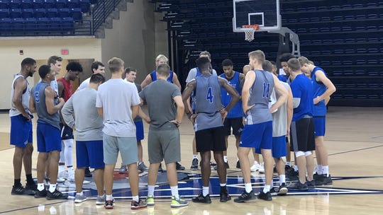 Coach Mike Morrell gathers the UNC Asheville men's basketball team.