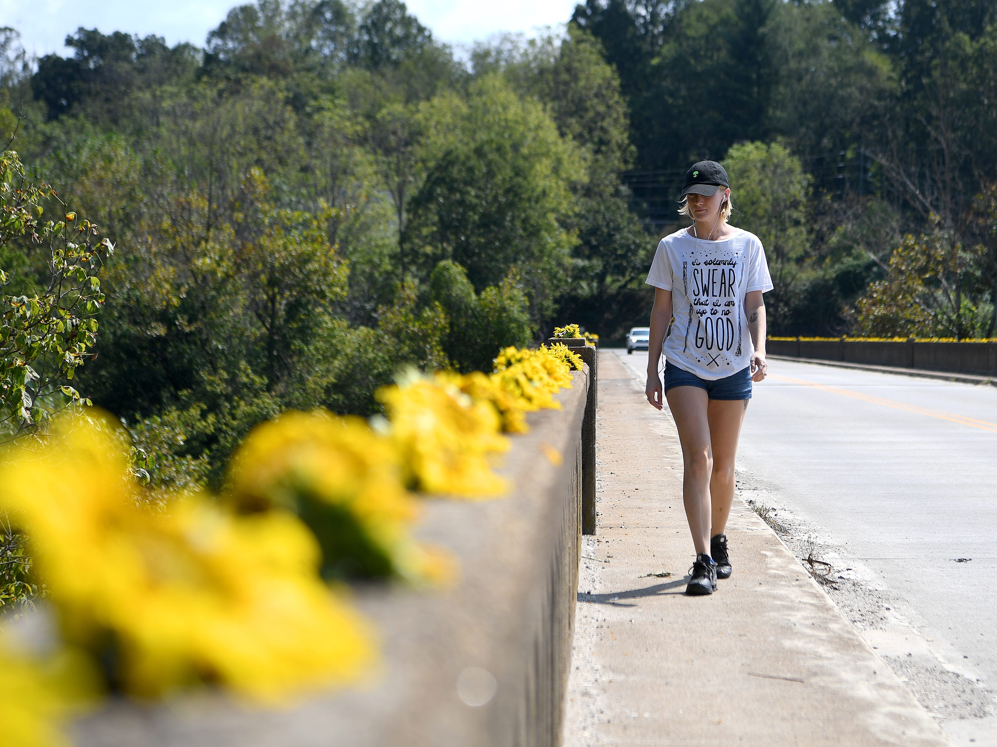 Lydia Powell walks down the Craggy Bridge in Woodfin to check out the row of flowers on the railings on Sept. 19, 2018. The flowers came from the organic farm in the Olivette community and were placed to simply spread joy and community.