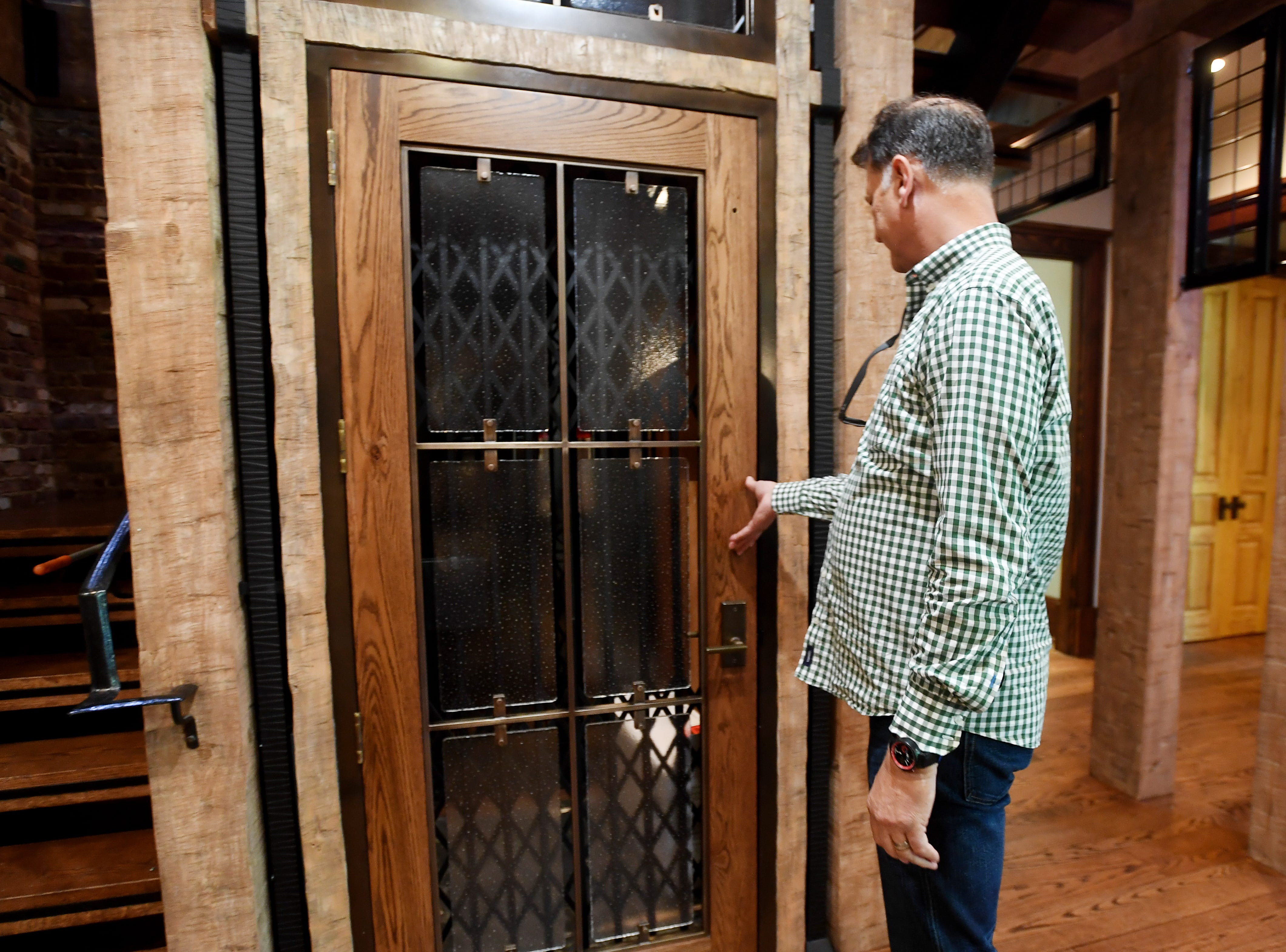 Ken Bowdon shuts the door of the elevator at his Balsam Mountain Preserve home.