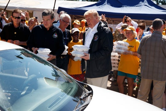 President Donald Trump and North Carolina Gov. Roy Cooper, left, hand out packaged meals to people in cars at Temple Baptist Church in an area impacted by Hurricane Florence on Sept. 19, 2018, in New Bern, N.C.