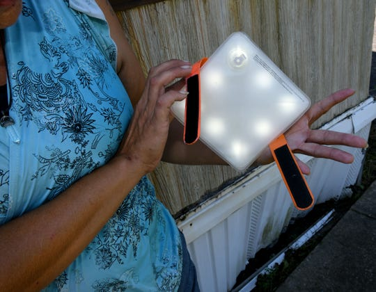 Mary Baisden shows off a solar light given to her by Chef José Andrés. The chef showed up in a police SWAT vehicle delivering food to her trailer where she and her boyfriend James Hinson live in Wilmington.