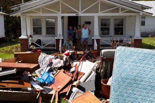 People sit outside their house during a visit by President Donald Trump to a neighborhood impacted by Hurricane Florence, on Sept. 19, 2018, in New Bern, N.C.