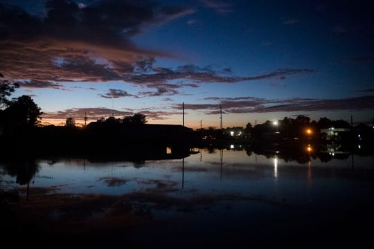 The sunset reflects on a flooded area between Judson Church Road and interstate 95 in Fayetteville, N.C., Tuesday, Sept. 18, 2018.