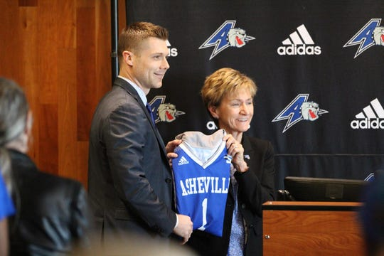 UNCA's new men's basketball coach Mike Morrell holds up a jersey with director of athletics Janet Cone.
