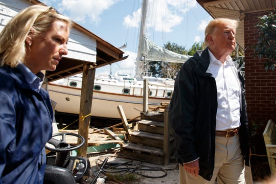 President Donald Trump visits a house where a boat wash ashore in the backyard while touring a neighborhood impacted by Hurricane Florence, on Sept. 19, 2018, in New Bern, N.C.