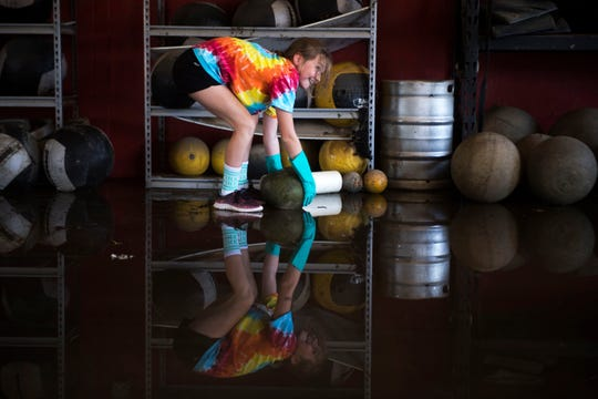 Hailey Maynard rolls a medicine ball while helping clean out Evolution Athletics East, which was flooded by the Little River after Florence, in Spring Lake N.C., on Sept. 19, 2018.
