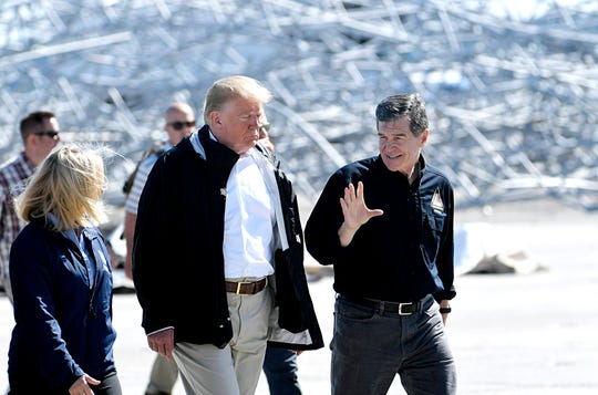 President Donald Trump walks with North Carolina Gov. Roy Cooper on the tarmac at Marine Corps Air Station at Cherry Point in Havelock, NC for a briefing on Hurricane Florence on Wednesday, Sept. 19, 2018