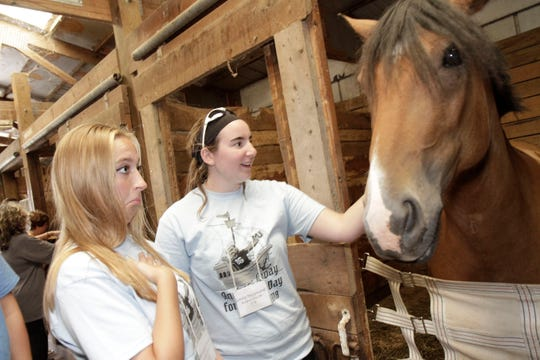 Misericordia University Orientation Leaders Michelle Artuso and Emily Hammond take time out during the eighth annual Misericordia Orientation Days of Service to make an equine friend at Serendipity Therapeutic Riding Center in Harveys Lake.