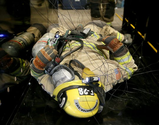 Navy Region Northwest firefighter Richard McClendon negotiates an entanglement of wires, while his mask is covered so he can't see, during a training exercise Wednesday at the Bremerton Readiness Center.