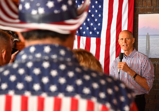 Rick Sarmiento of the Bikers United Coalition, attired in a flag-themed shirt and hat, watches Gov. Rick Scott speak during a campaign stop in Titusville for his U.S. Senate race against incumbent Bill Nelson.
