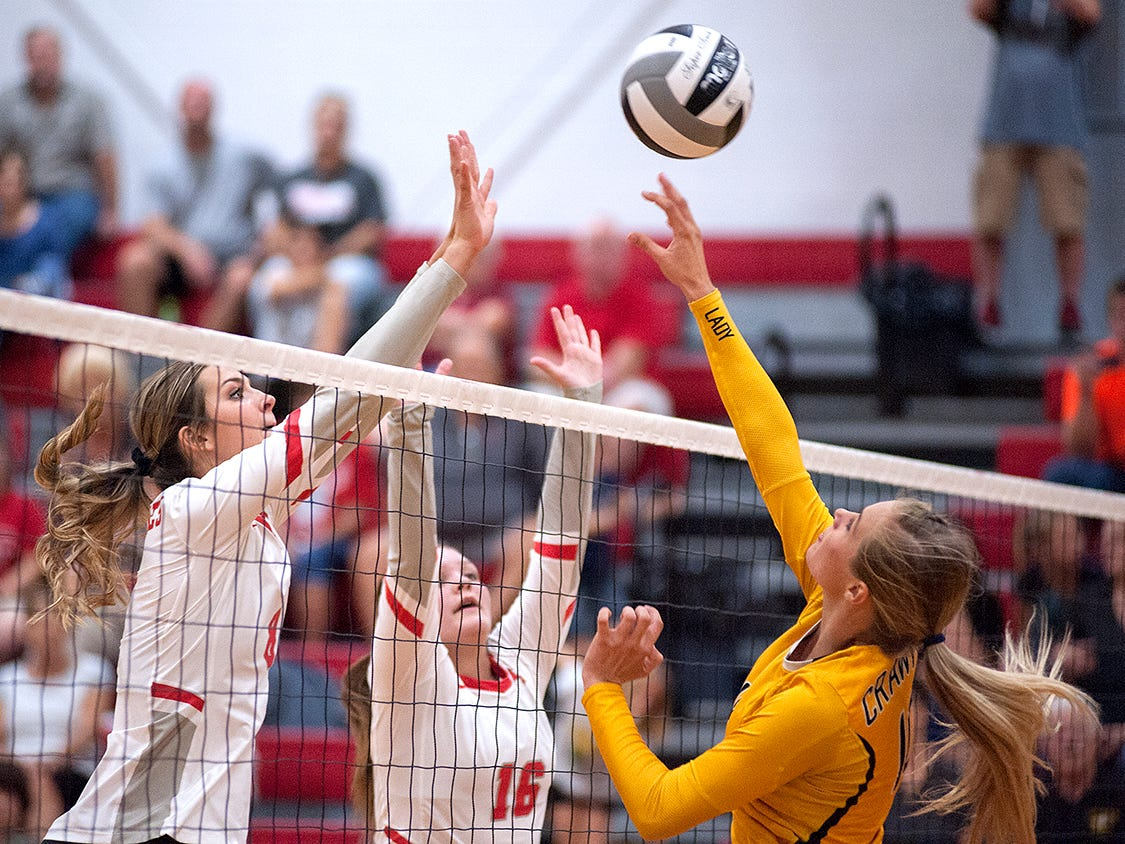 A hit by Colonel Crawford's Keirsten O'rourke is blocked by Buckeye Central's Lexi Evak and Allyson Sostakowski.
