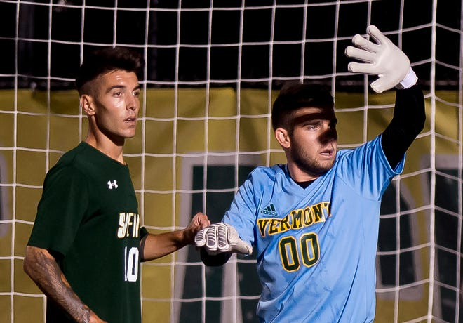 Vermont goalie Clay Thomas, right, shields his eyes for a corner kick by Siena during Tuesday night's men's soccer game at Virtue Field.
