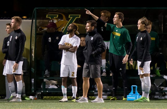 The University of Vermont bench watches the action late in the second half against Siena during Tuesday night's men's soccer game at Virtue Field.