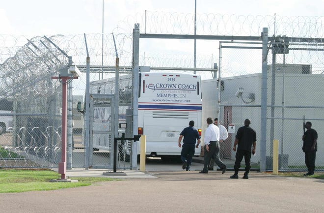 Caption: Tallahatchie County Correctional Facility guards prepare to inspect the last of three buses bringing 150 Hawaiian prisoners from Arizona facilities as it enters the unloading area Tuesday, May 18, 2004, in Tutwiler, Miss. Mayor Robert Grayson says he's confident the operators of the private prison in his town can handle any problems that might arise now that maximum security inmates are kept there. (AP photo/Clarksdale Press Register/Troy Catchings)