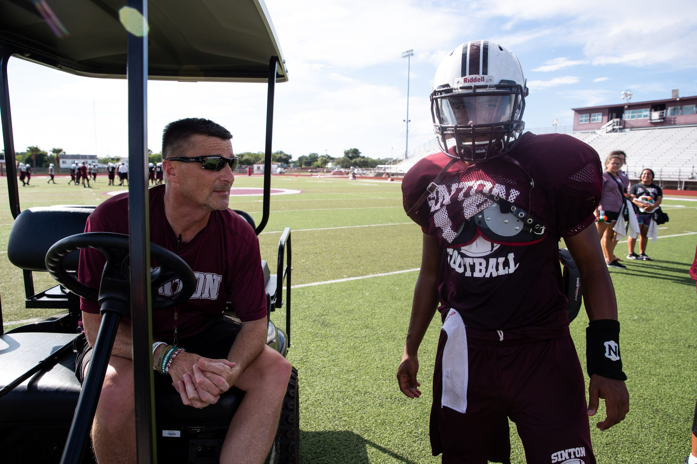 Tom Allen head coach of the Sinton football team talks to one of his players as he sits in his cart during practice at Sinton High School on Tuesday, Sept. 18, 2018. Allen is suffering from a rare neurological disease that has him in a cart during games and practices