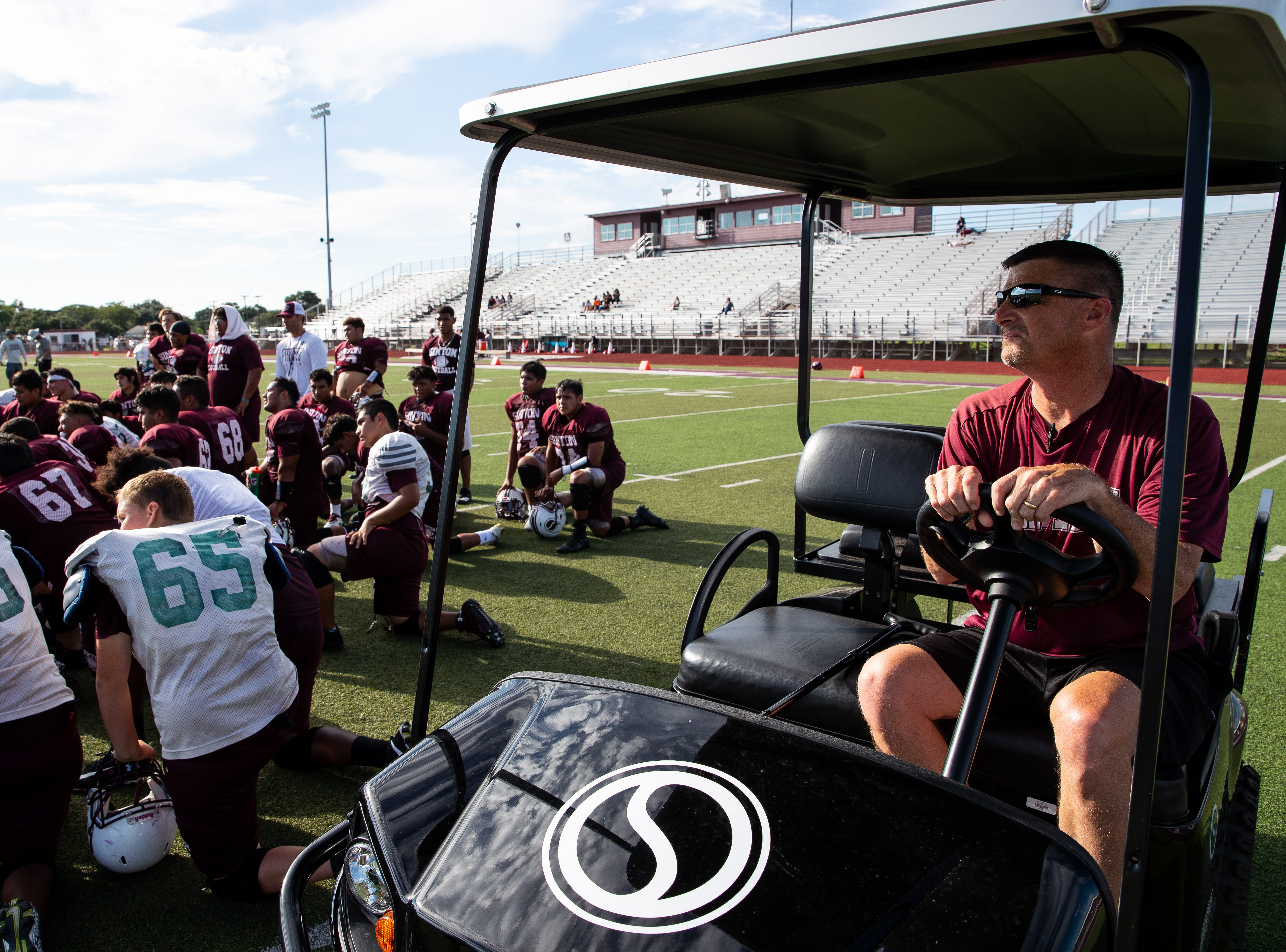Tom Allen head coach of the Sinton football team sits in his cart as the teams huddles after running plays on the field during practice at Sinton High School on Tuesday, Sept. 18, 2018. Allen is suffering from a rare neurological disease that has him in a cart during games and practices