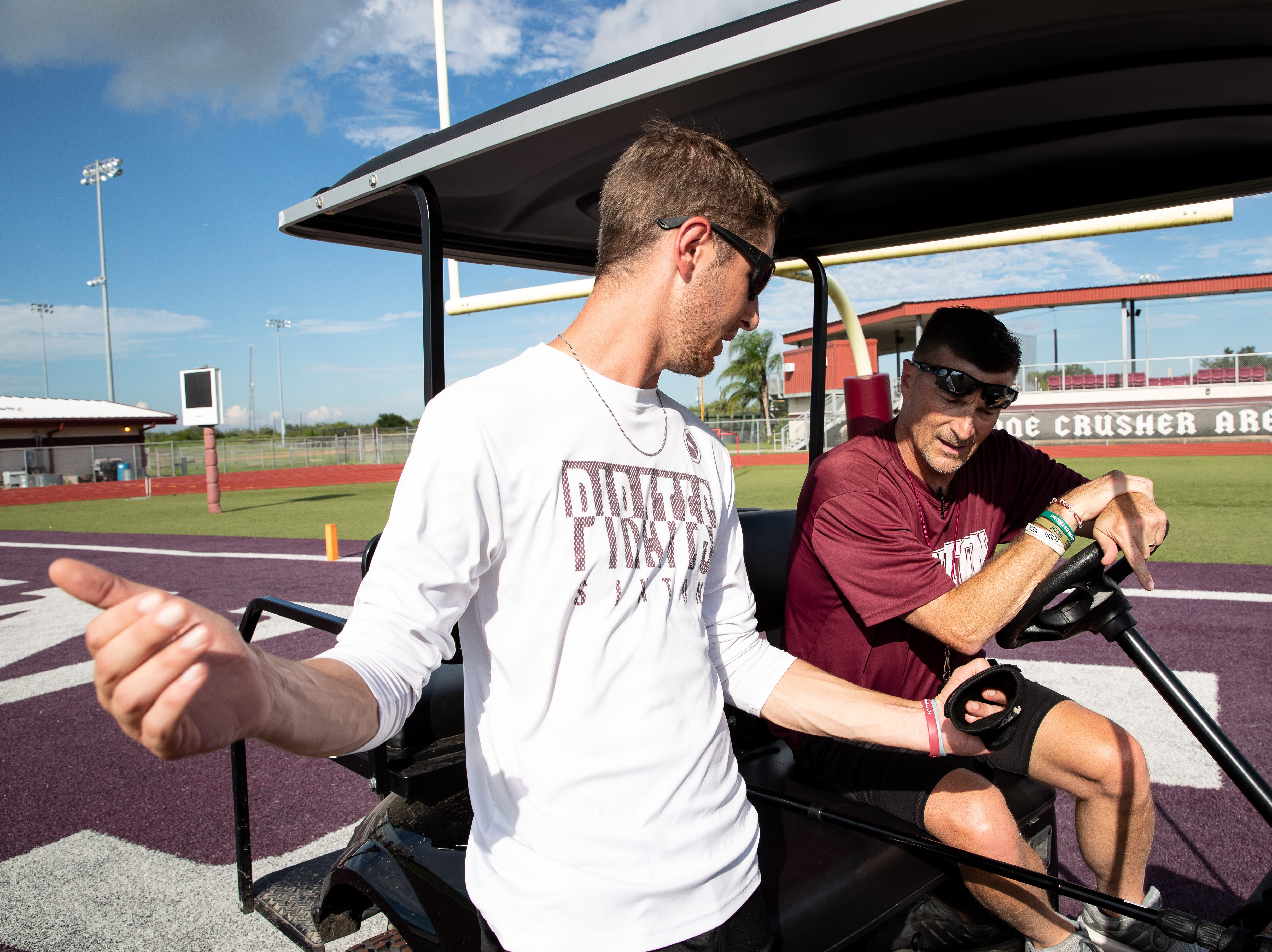 wide receiver coach Brian Allen checks a play with his Tom Allen head coach of the Sinton football during practice at Sinton High School on Tuesday, Sept. 18, 2018. Allen is suffering from a rare neurological disease that has him in a cart during games and practices