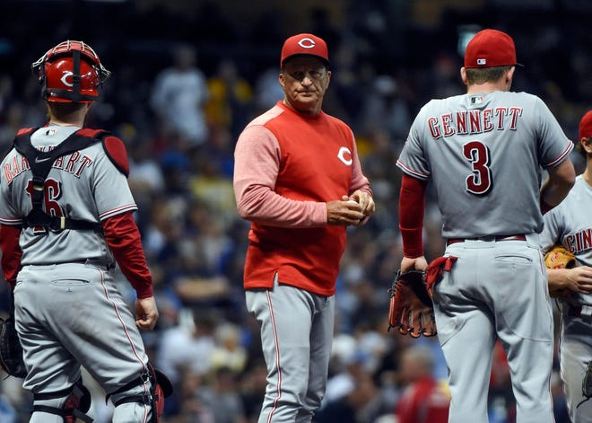 Sep 18, 2018; Milwaukee, WI, USA; Cincinnati Reds manager Jim Riggleman talks to catcher Tucker Barnhart (16) and second baseman Scooter Gennett (3) during a pitching change in the seventh inning during the game against the Milwaukee Brewers  at Miller Park. Mandatory Credit: Benny Sieu-USA TODAY Sports