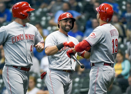 Sep 18, 2018; Milwaukee, WI, USA;  Cincinnati Reds shortstop Jose Peraza (9) is greeted by first baseman Joey Votto (19) and right fielder Scott Schebler (43) after hitting a two run home run in the first inning against the Milwaukee Brewers at Miller Park.