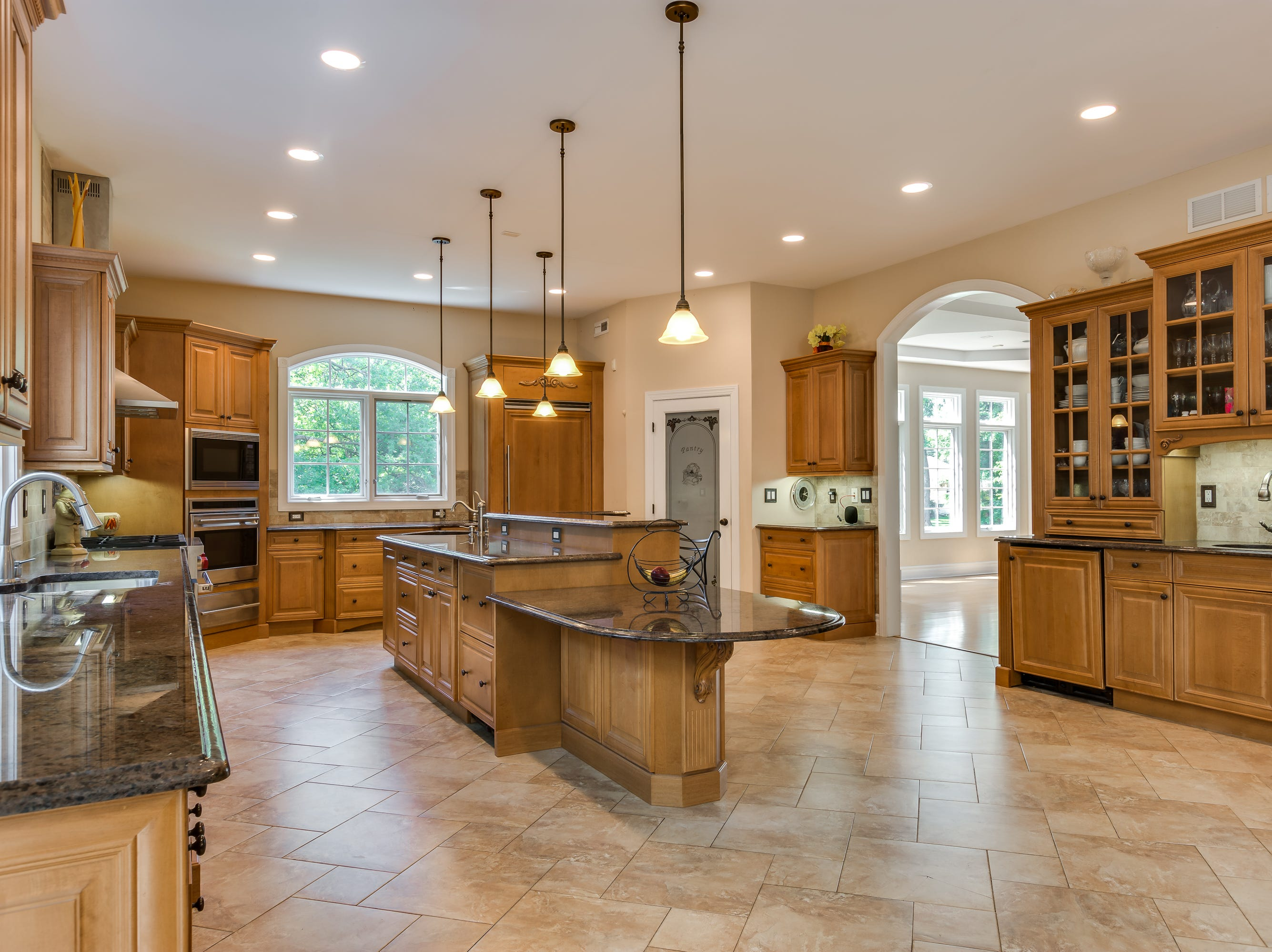 The kitchen has a center island with three tiers, a wealth of maple cabinets, pendant and recessed lighting and granite counters. The appliances all are professional grade.