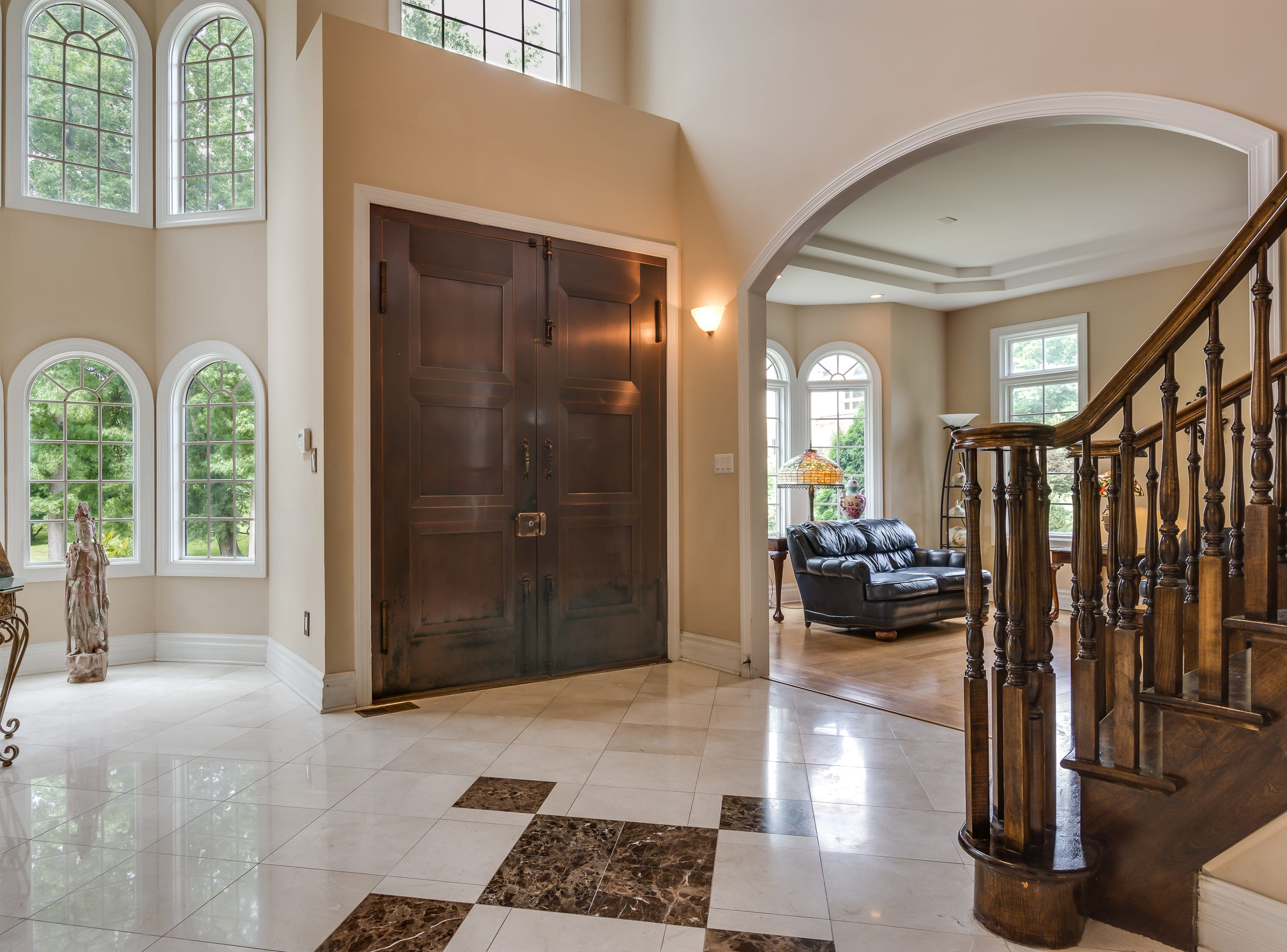 The two-story foyer features a marble floor and a winding maple staircase to the second floor and its balcony overlook. Through the arch, you can see the formal living room with its bamboo floor and tray ceiling.