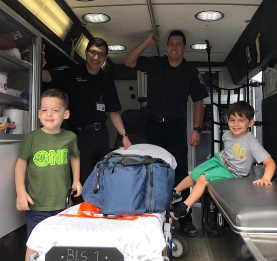Joey Reinel, 3, (left) with his twin brother Julian (right), visits with Old Bridge EMTs  Matthew Ackerman and Tom Barrett who helped saved his life Aug. 19.