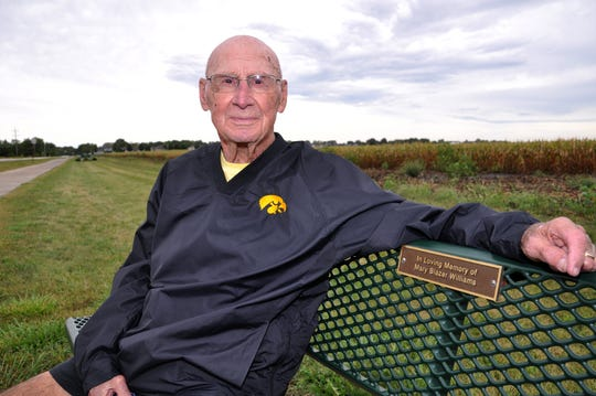 Bob Williams of Long Grove, Iowa, sits at the memorial bench to his late wife, Mary, where he often hands out chocolate bars to random walkers on the trail.
