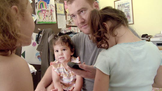 """In a frame grab from the movie """"The Sentence,"""" Adam Shank holds the phone so his daughters Autumn, Annalis and Ava can talk with their mother Cindy, who was in jail."""