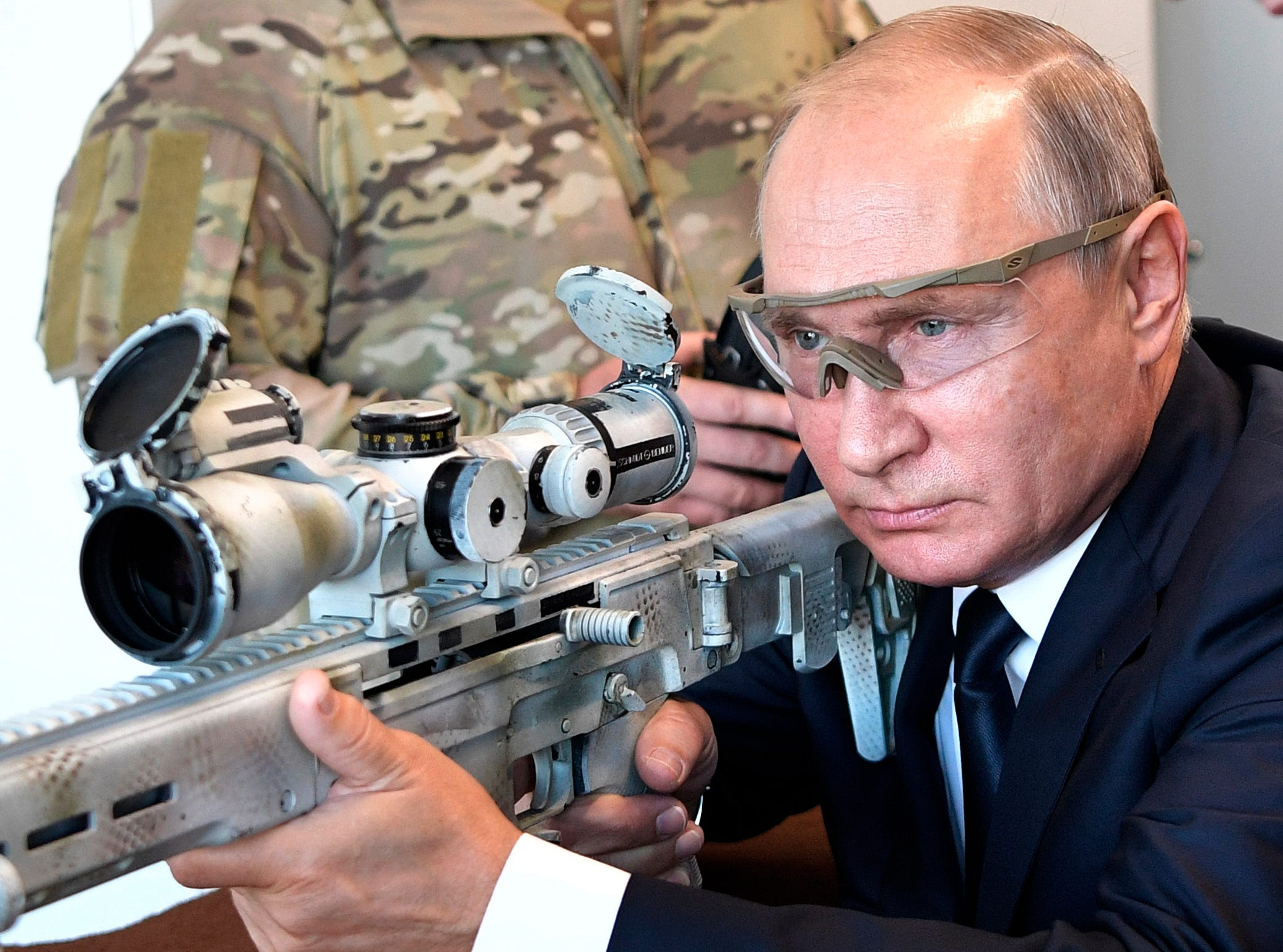 Russian President Vladimir Putin aims a sniper rifle during a visit to the Patriot military exhibition center outside Moscow on Wednesday, Sept. 19, 2018. Putin chaired a meeting that focused on new arms programs.