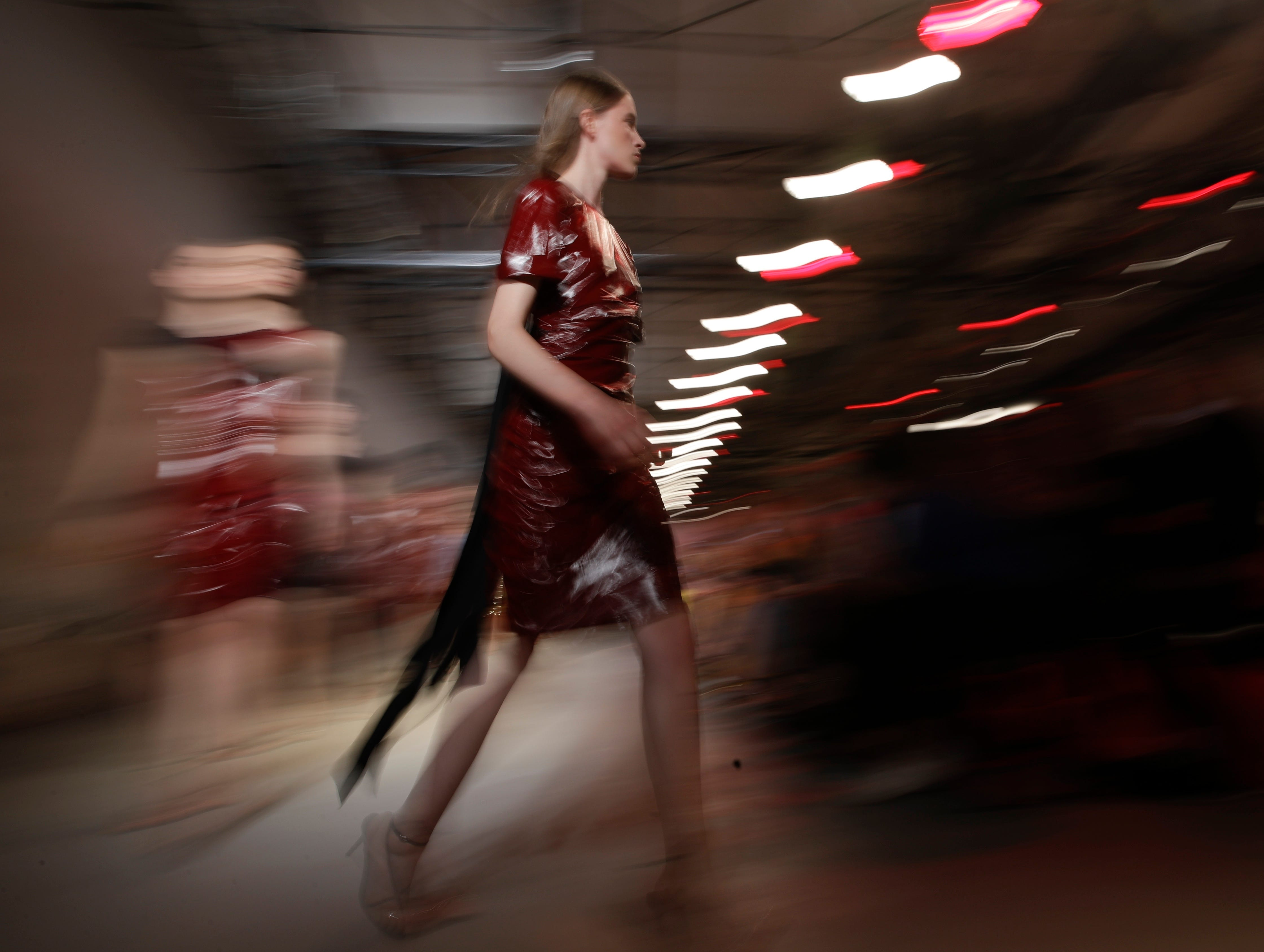 In this photo taken with slow shutter speed, a model wears a creation as part of the N.21 women's 2019 spring-summer collection, unveiled during Fashion Week in Milan, Italy, Wednesday, Sept. 19, 2018.