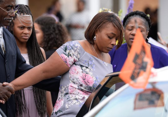 Danyna Gibson's mother is escorted to the car after her 16-year-old daughter's funeral service in Warren Wednesday.