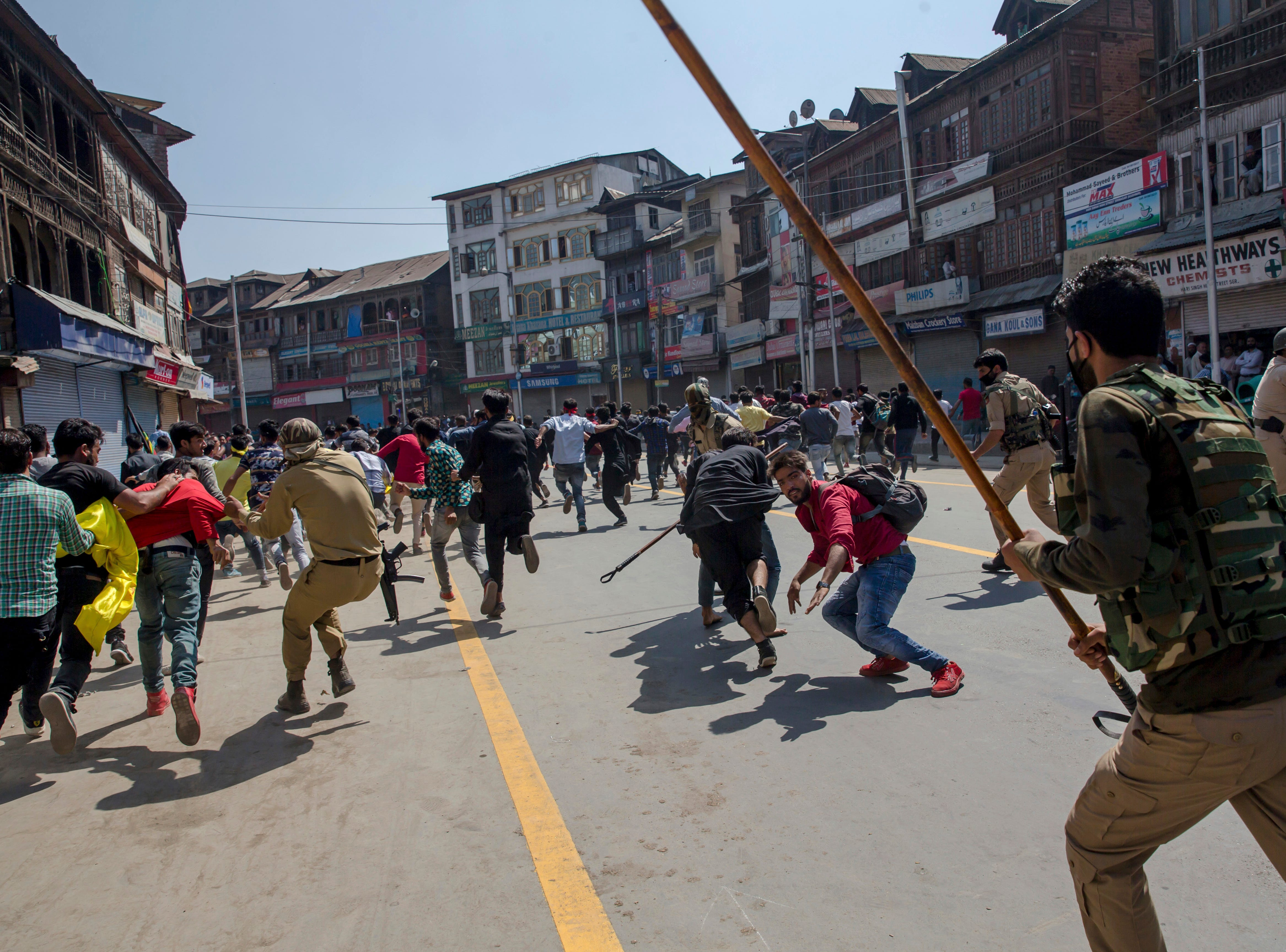 Indian policemen charge at Shiite Muslims participating in a religious procession in central Srinagar, Indian-controlled Kashmir, Wednesday, Sept. 19, 2018.