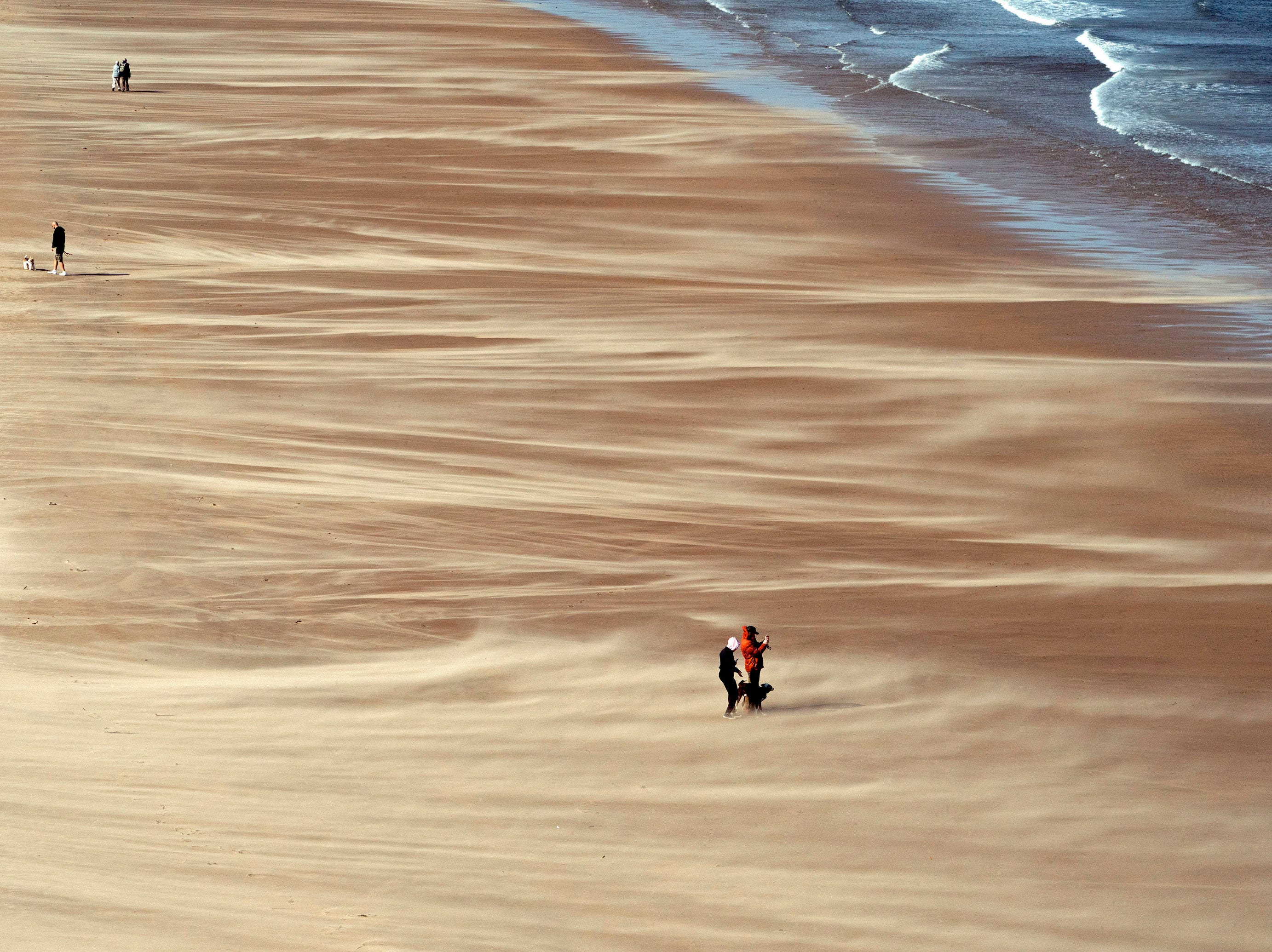 People walk along Tynemouth Beach on the northeast coast of England, as forecasters warn about strong storm winds across the region on Wednesday Sept. 19, 2018.  An amber warning was issued, covering Northern Ireland and northern parts of England and Scotland.