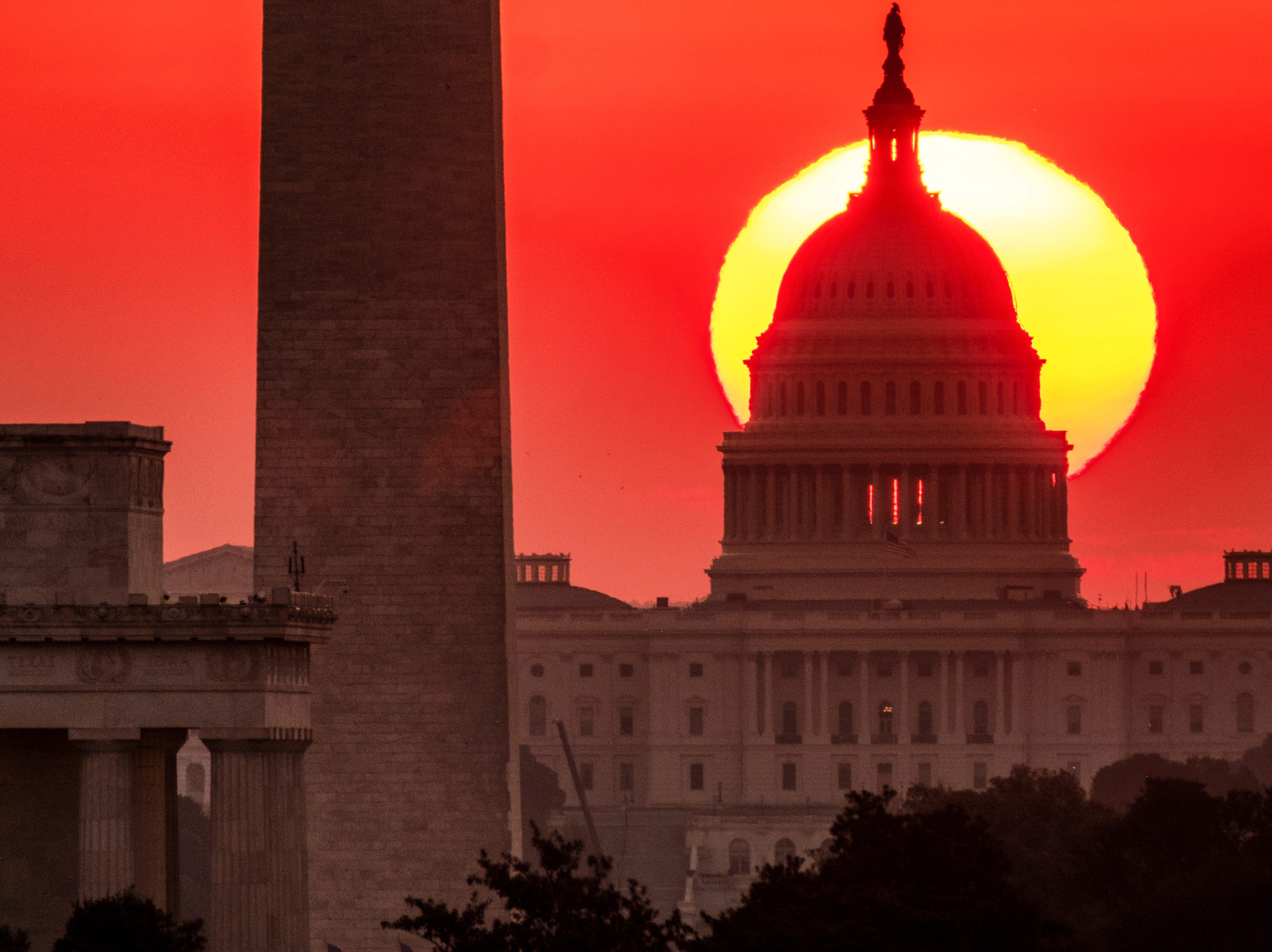 The sun rises behind the U.S. Capitol in Washington at dawn Wednesday, Sept. 19. 2018.