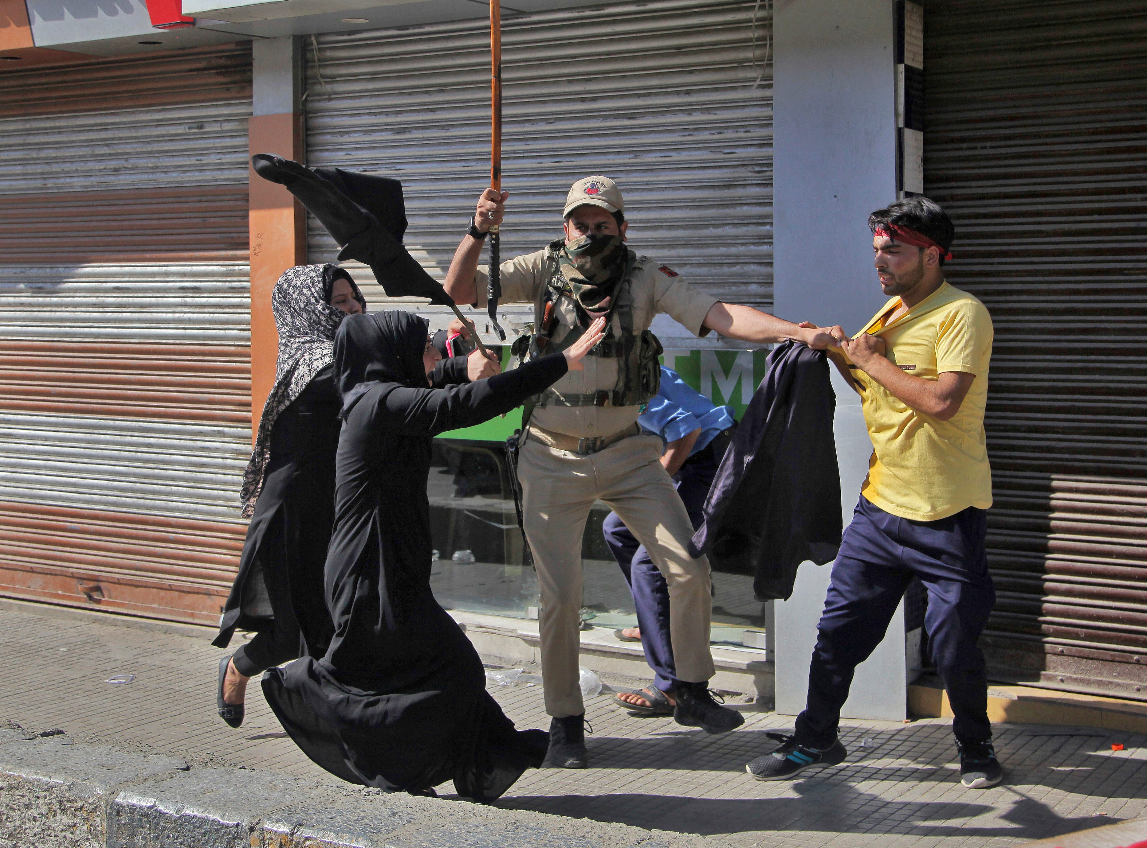 Shiite Muslim women rush to rescue a youth being detained by a policeman  during a Muharram procession in Srinagar, Indian-controlled Kashmir, Wednesday, Sept. 19, 2018. Police and paramilitary soldiers on Wednesday used batons and fired tear gas to disperse hundreds of Muslims participating in religious processions.