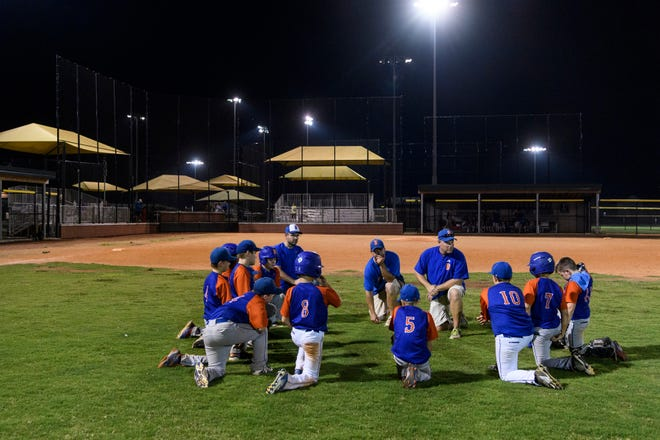 The Bases Loaded Bombers of Washington, Ind., discuss their loss against the River City Aces of Evansville, not pictured, during an Indiana USSSA fall ball baseball league game at Deaconess Sports Park in Evansville, Ind., Tuesday, Sept. 18, 2018.