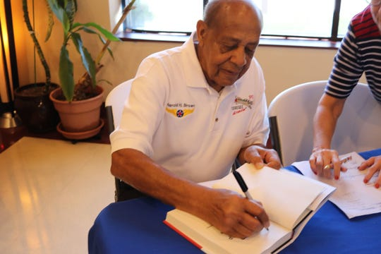 """Former Tuskegee Airman retired Lt. Colonel Dr. Harold Brown signs a copy of his book, """"Keep Your Airspeed Up: The Story of a Tuskegee Airman,"""" in September 2017."""