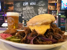 Monster sized ZZQ sandwich is piled high with brisket, pulled pork and beer cheese sauce