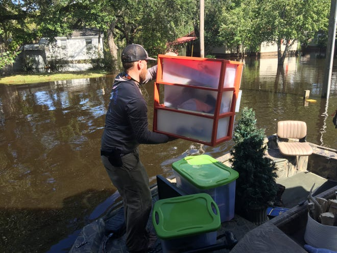 McCarthy Huggins stacks boxes from Whitney Hall's house in Conway on a boat headed for dry land as floodwaters rise around Hall's home on Tuesday, September 18, 2018.
