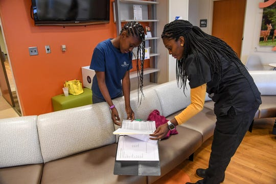 Kaimora Smith, 13, of Mauldin looks over her notebook with her mother Sharee Gray after getting a Doppler brain scan from Dr. Alan Anderson at the Cancer Institute at the Greenville Health System in Greenville in September.