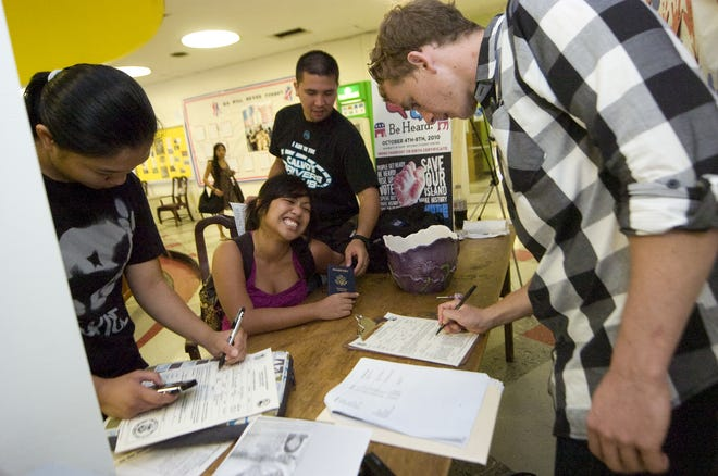 In this October 2010 file photo, University of Guam students Kat Ricarte, left, and Komekha Cadag, seated, register to vote at the student center. Registrars will be at the university Sept. 25 and Sept. 26 for National Voter Registration Day.