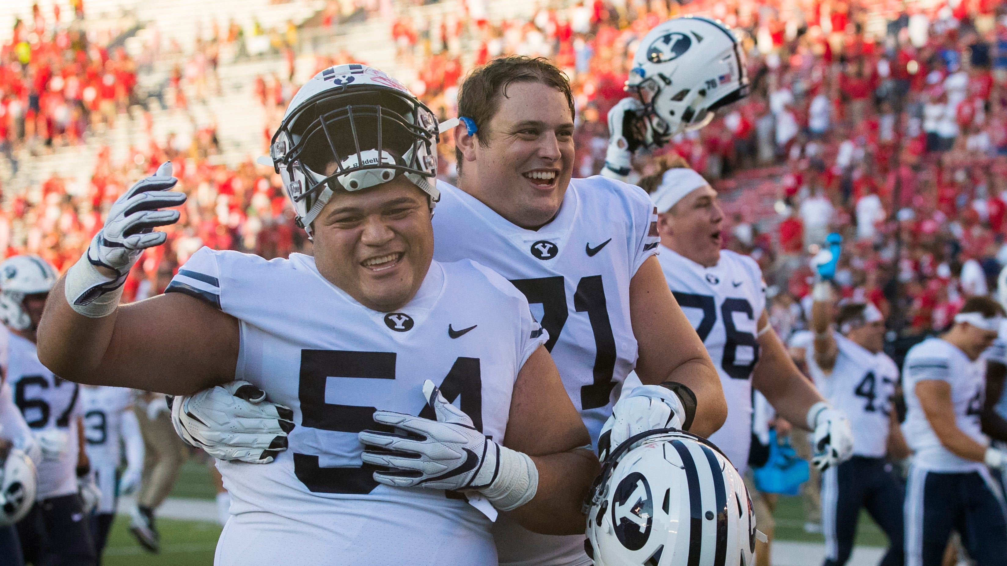 BYU defensive lineman Merrill Taliauli (54) and offensive lineman Austin Hoyt (71) celebrate their 24-21 win at Wisconsin. How did they pull it off? Limiting mistakes was a good start.