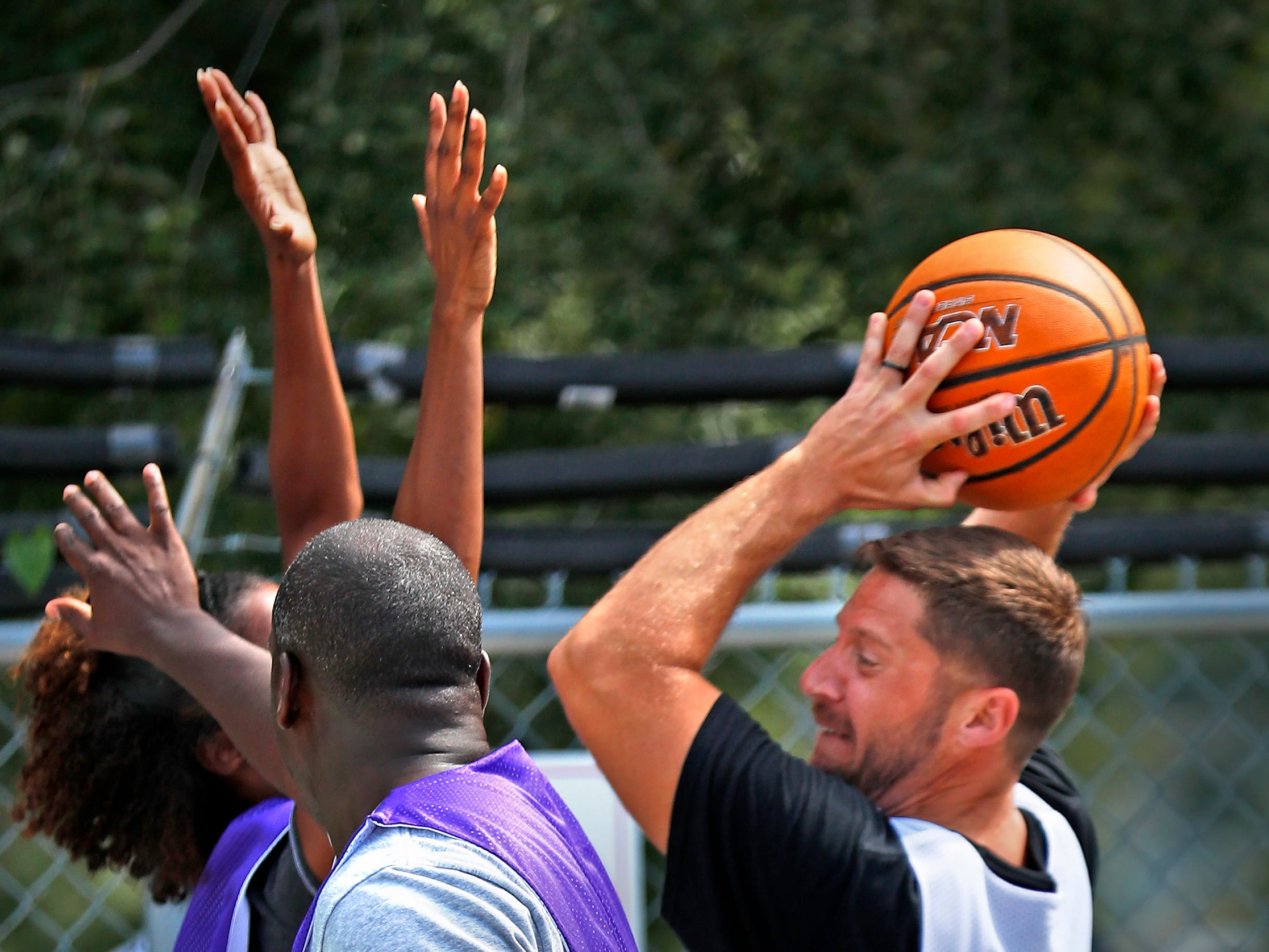Bryan Bush, right, with Goodwill, shoots over his opposition, during a basketball game at Goodwill Commercial Services, Wednesday, Sept. 19, 2018.  Goodwill Industries of Central Indiana's New Beginnings hosted the 3-on-3 basketball tournament bringing together participants in New Beginnings, a six-month re-entry program for ex-offenders that works on job and life skills, with representatives from Goodwill, IMPD, the Mayor's office, Marion County Probation department and other services.  The goal is to celebrate the New Beginnings program while breaking down re-entry barriers through basketball.