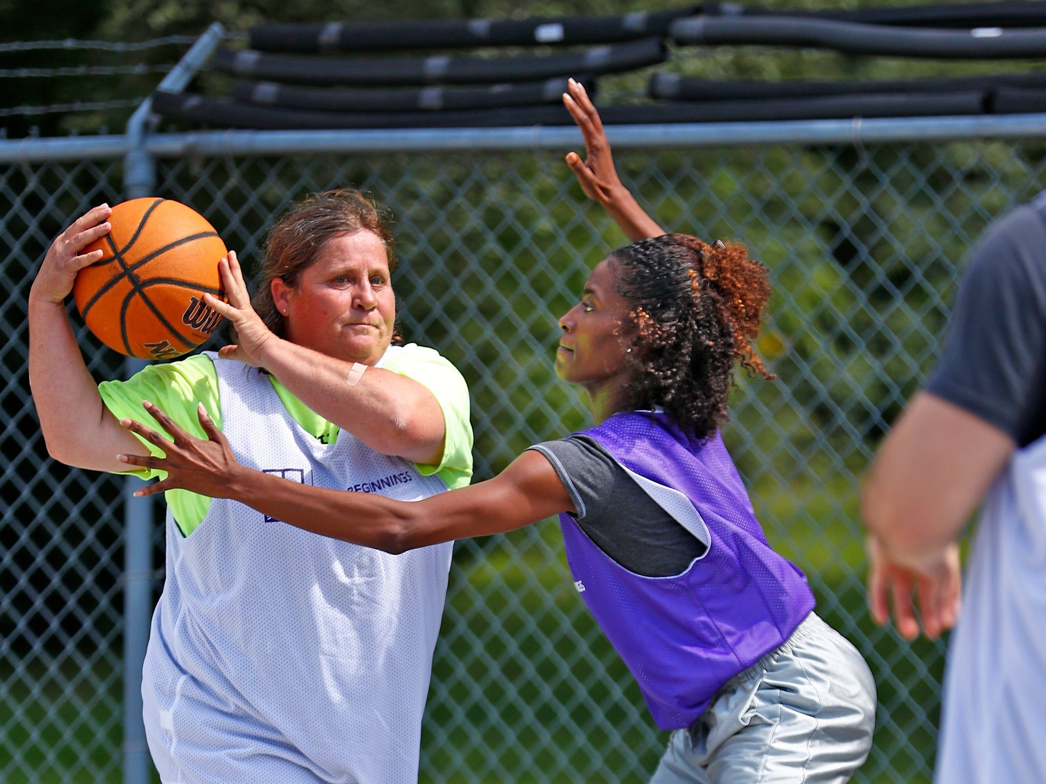 Tonya Surber, left, and Alexaundria Monroe, both with Marion County Probations, play during a basketball game at Goodwill Commercial Services, Wednesday, Sept. 19, 2018.  Goodwill Industries of Central Indiana's New Beginnings hosted the 3-on-3 basketball tournament bringing together participants in New Beginnings, a six-month re-entry program for ex-offenders that works on job and life skills, with representatives from Goodwill, IMPD, the Mayor's office, Marion County Probation department and other services.  The goal is to celebrate the New Beginnings program while breaking down re-entry barriers through basketball.